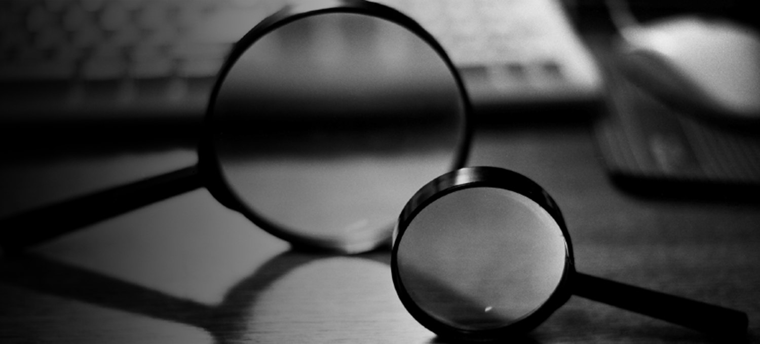 A black and white photo of two spying glasses laying on a desk